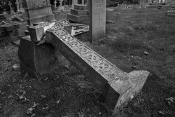 Cemetery cross fallen and broken in black and white