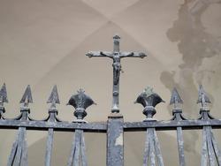 Cemetery. Iron gate, detail. Jesus on the cross.