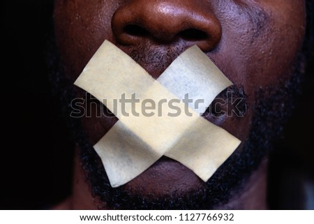 Censorship concept. Black Man is silenced with adhesive tape across his mouth. Silence #1127766932