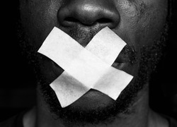 Censorship concept. Black Man is silenced with adhesive tape across his mouth. Silence. Black and white