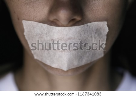 Censorship in the Modern World: A man's mouth sealed with an adhesive tape, close-up