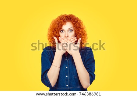 Censorship. Speak no evil concept. Concerned scared redhead woman curly afro hair covering her mouth with hands in blue jeans shirt isolated on yellow background Stock photo ©