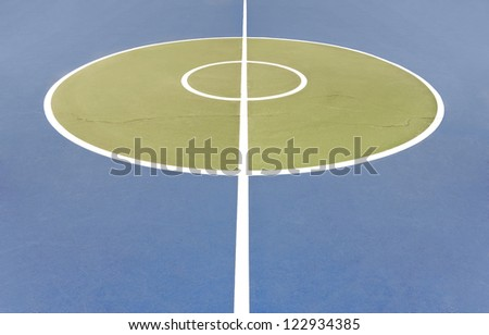 Center court. A white line and two circles mark the center of an outdoor basketball court. A long crack in the painted concrete runs through the court. Horizontal view.