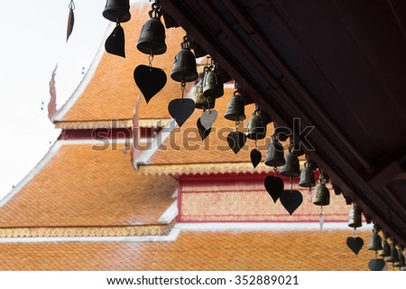 Center focus onto bells with heart plate hang on roof of public temple #352889021
