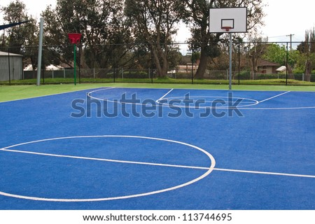 Center of basketball in bright green and blue, synthetic grass carpet surface with white lines and training basket #113744695