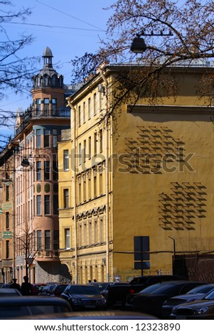 Center of city. Old houses, cars and wall of old house with strange iron construction which cast strict geometrical shadows.