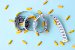 centimeter tape and pills on a colored background with space for text. concept of losing weight, diet, fat burning, healthy eating. minimalism.