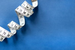 Centimeter tape, fitness and weight loss. Tailor's meter, for sewing, on a blue background. Meter, tape measure, to measure the body, waist in centimeters.