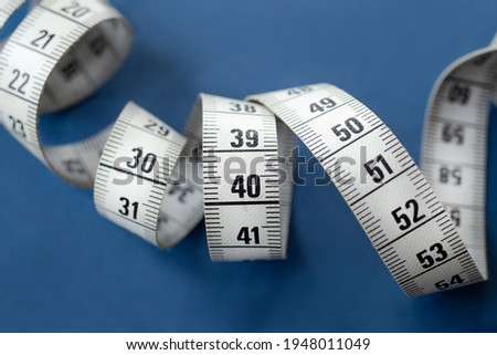 Centimeter tape, fitness and weight loss. Tailor's meter, for sewing, on a blue background. Meter, tape measure, to measure the body, waist in centimeters. Foto d'archivio ©