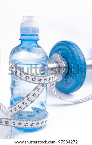 Centimeter wrapped around bottle of water and dumbbell in the background, on the white background - stock photo