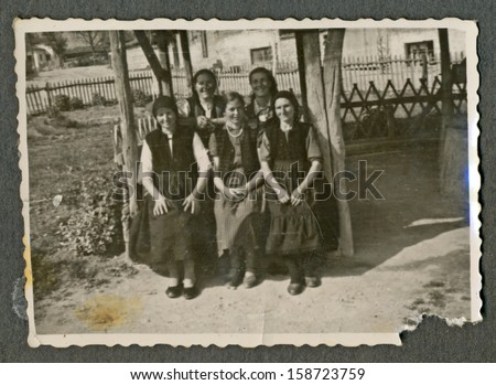 CENTRAL BULGARIA, BULGARIA - CIRCA 1950: Five young women sitting on an old wooden bench (possibly swing) and smile at the photographer - Note: slight blurriness, better at smaller sizes - circa 1950