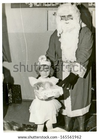 CENTRAL BULGARIA, BULGARIA - CIRCA 1980 - In kindergarten, Santa Claus (Papa Frost or Papa Noel) visited the kid (a girl) - Note: slight blurriness, better at smaller sizes - circa 1980