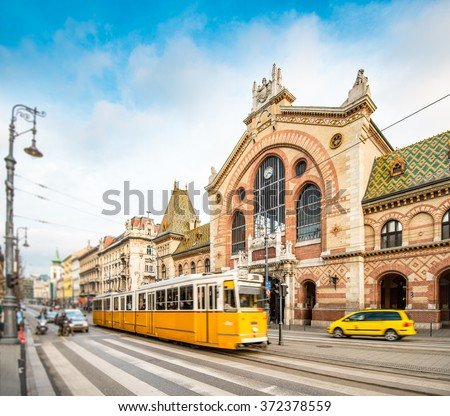 Central Market Hall in Budapest city, Hungary, Europe. Pedestrian crossing and yellow tram in foreground, old building and blue sky in background. #372378559