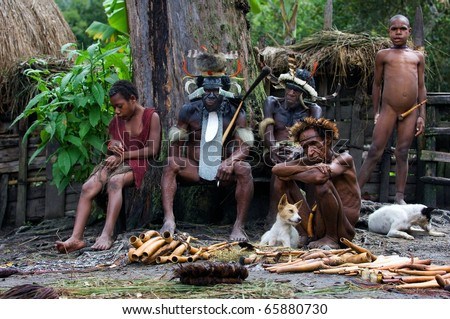 CENTRAL PAPUA NEW GUINEA , INDONESIA - JULY 2: New Guinean natives Dani of a tribe sit on a bench in Village of people Dani Dugum. Yali Mabel - Chief of Dani tribe.Papua New Guinea. July 2, 2009.