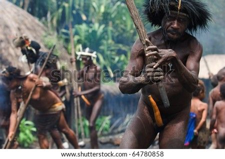 CENTRAL PAPUA, NEW GUINEA - JUNE 25: The Papuan banishes from the village, swinging a stick. Indonesia. Village of people Dani Dugum. On June, 2009 in Papua New Guinea.