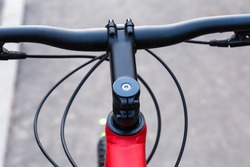 Central part of handlebar and node of connect his to fork stem of modern bicycle, top view close-up in selective focus