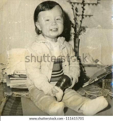 Central Slovakia, CZECHOSLOVAK REPUBLIC, CIRCA 1974 - baby sitting on a blanket - circa 1974