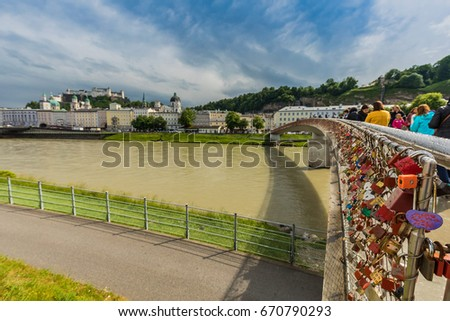 Century-old tradition of inscribing a lock with lover's initials, affixing it to a popular bridge and tossing the key into the river to symbolize their eternal love. At Makartsteg footbridge, Salzburg #670790293