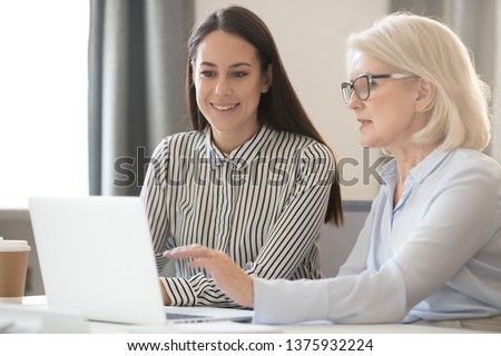 Ceo female in glasses show to intern millennial girl corporate program task use pc, senior woman executive leader supervising teaching colleague, mentor share knowledge helping to new employee concept