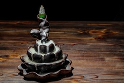 Ceramic backflow incense burner in the form of lotus flower. Incense cones holder. Dark mystic concept.