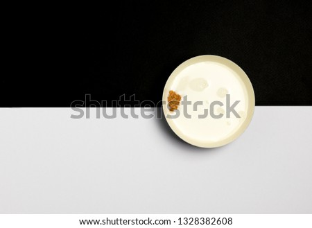 Ceramic bowl filled with milk and a piece of healthy cereal on a black and white background. Concept of healthy breakfast #1328382608