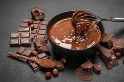 ceramic bowl of chocolate cream or melted chocolate and pieces of chocolate on dark concrete background