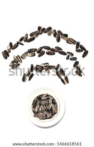 Ceramic bowl with black sunflower seeds. Seeds and a plate form a wi fi mark (sign, symbol). Vertically. #1466618561