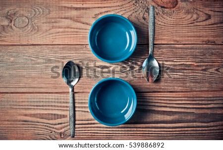 Ceramic bowls for baking and spoons . Kitchen composition. Cutlery and table utensils. The process of cooking. Wooden background.