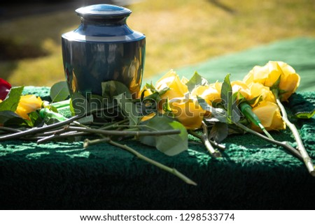 Ceramic burial urn with yellow roses, in a morning funeral scene, with space for text on the right