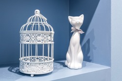 ceramic cat and metal cage in the recess of the blue wall in the apartment