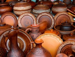 Ceramic clay brown terracotta jug, pot, plate, cup kitchen souvenirs pile at street handicraft pottery shop. Old earthen terracotta plate, jug, pot, clay jar pattern in store. Clay various ceramic pot