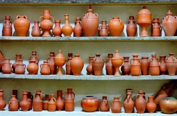 Ceramic clay terracotta jug, pot, vase, kitchen souvenirs on shelf at street handicraft pottery shop. Old earthen terracotta jug, pot, clay jar pattern in store. Clay brown various ceramic pot & jugs
