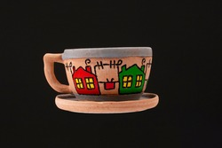Ceramic coffee cup isolated on black background. Pottery art tea cup with artist paintings and graving