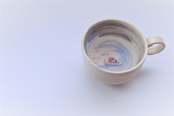 Ceramic cup designed as a blue watermark inside. There is a small koi fish statue is swimming into the bottom of the glass. Lovely and creative craft concept.