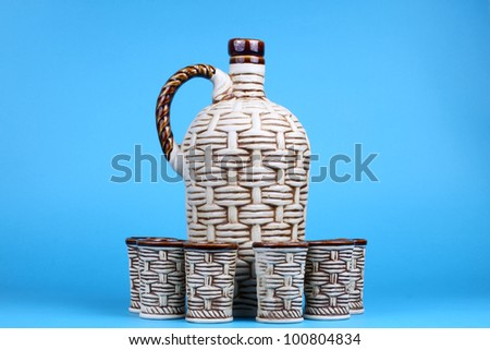 Ceramic decanter and glass with wine on blue background
