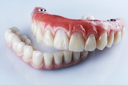 ceramic dental dentures of the upper and lower jaws for fixation on four implants on a white background