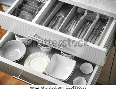 Ceramic dishware and cutlery in kitchen drawers #1114330052