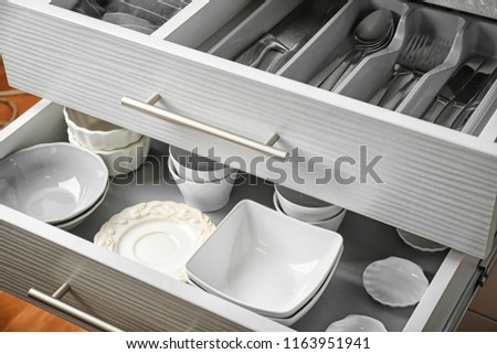 Ceramic dishware and cutlery in kitchen drawers #1163951941
