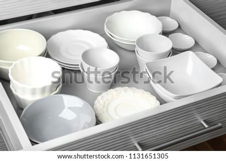 Ceramic dishware in kitchen drawer #1131651305