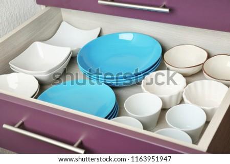 Ceramic dishware in kitchen drawer #1163951947