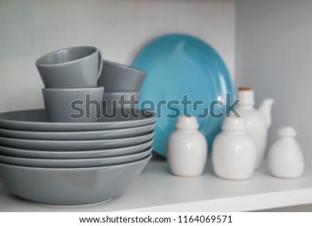 Ceramic dishware on white shelf indoors #1164069571