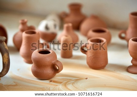 Ceramic dishware on worktop and shelves in pottery workshop, selective focus, close-up #1071616724