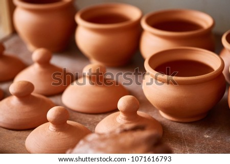 Ceramic dishware on worktop and shelves in pottery workshop, selective focus, close-up #1071616793
