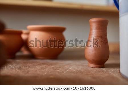 Ceramic dishware on worktop and shelves in pottery workshop, selective focus, close-up, shallow depth of field #1071616808