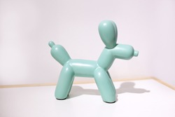 Ceramic dog doll on a white background. statuette of a dog in mint color stands on a table against a white wall in the interior of the house.. Ceramic figurine, dog breed isolated on white. Home decor