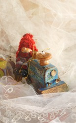 Ceramic doll in a red hat on a toy wooden train. Girl in a hurry to the holiday. Festive decorations for the New Year. Ideas To Capture the Festive Mood of The Winter Season. Openwork white background