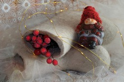 Ceramic doll in a warm red hat. Winter felt boots for the kid in New Year decorations. Good Mood During The Winter Holidays. Magic time for fulfilling your wishes. Merry Christmas