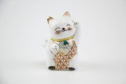 Ceramic doll style Japanese welcoming lucky Cat. ( Maneki Neko ):Japanese characters means good luck or fortune on white background .