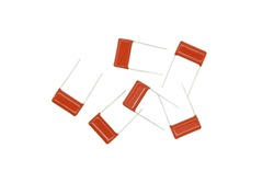Ceramic electronic capacitors for soldering to a printed circuit board are isolated on a white background