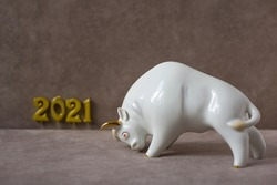 Ceramic figurine of white bull on brown background next to the golden numbers 2021. Bull symbol of the year 2021